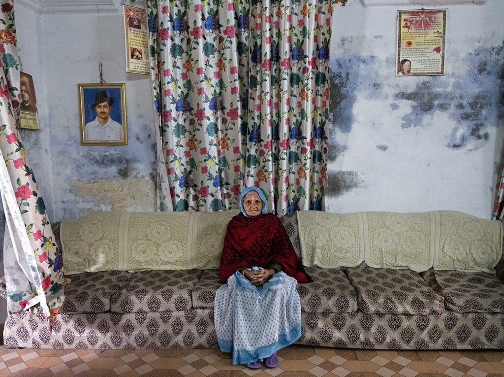 A widow sitting in the couch in Durga Kund Help Line ashram