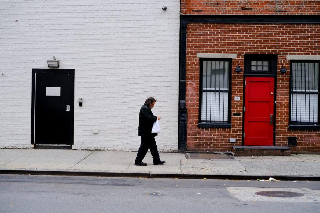pedestrian in black on the sidewalk
