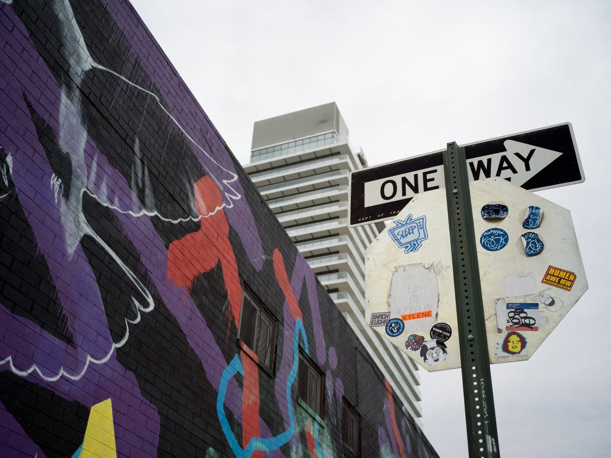 One way sign next to wall covered in graffiti