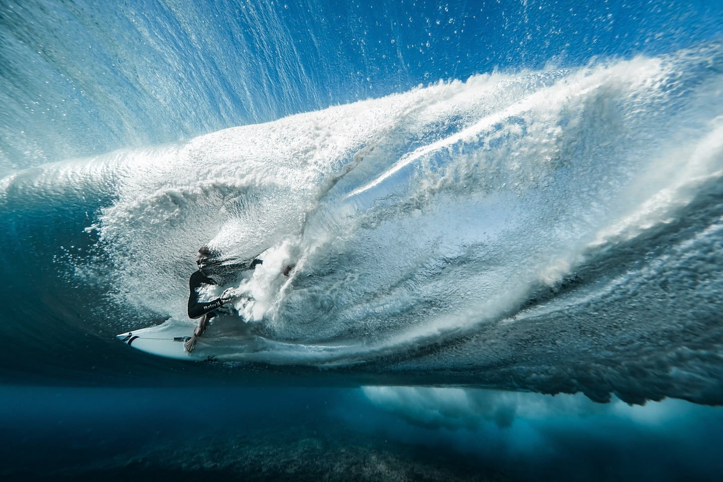 underwater shot of Ace Buchan kicking out from the barrel through the wave