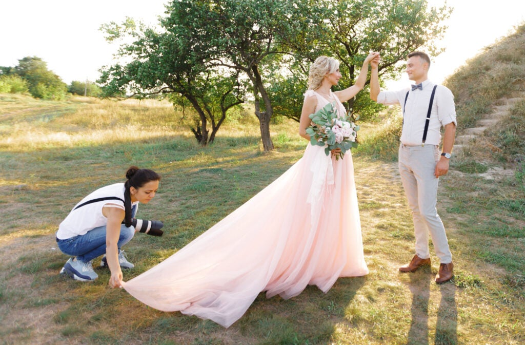 wedding photographer takes pictures of bride and groom in nature.