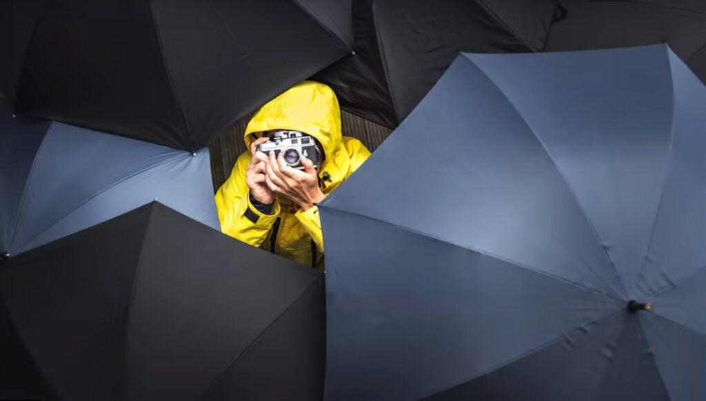 photography umbrellas around photographer in rain coat