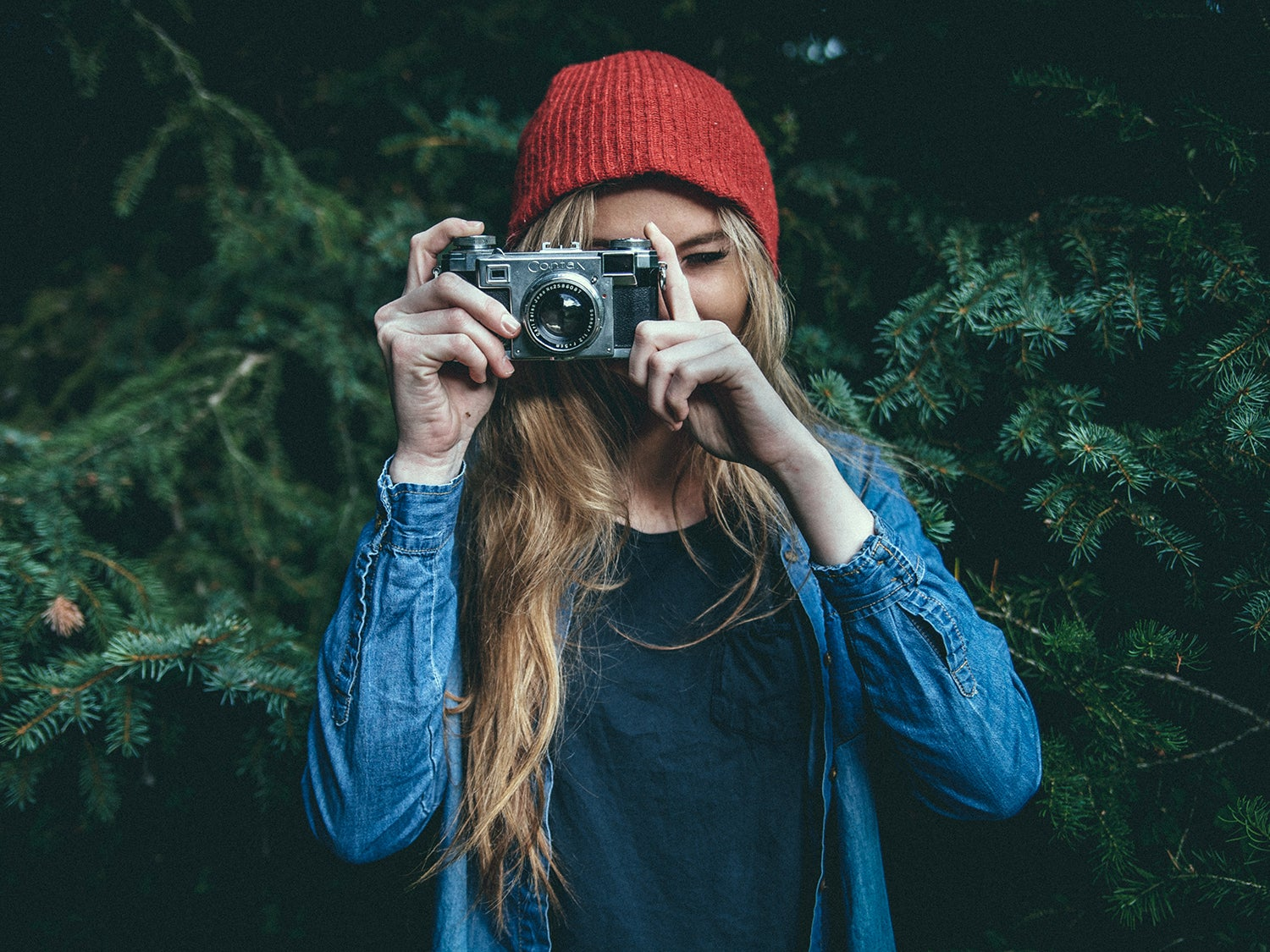 photographer in red hat against evergreen trees
