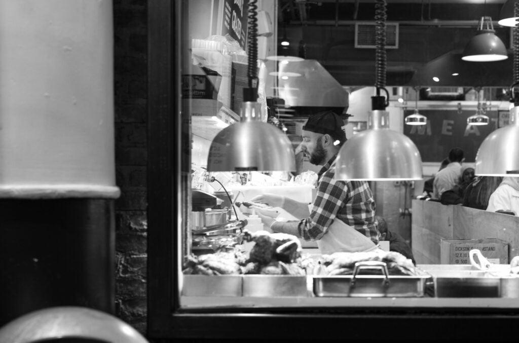 A man prepares fancy hot dogs in Chelsea Market