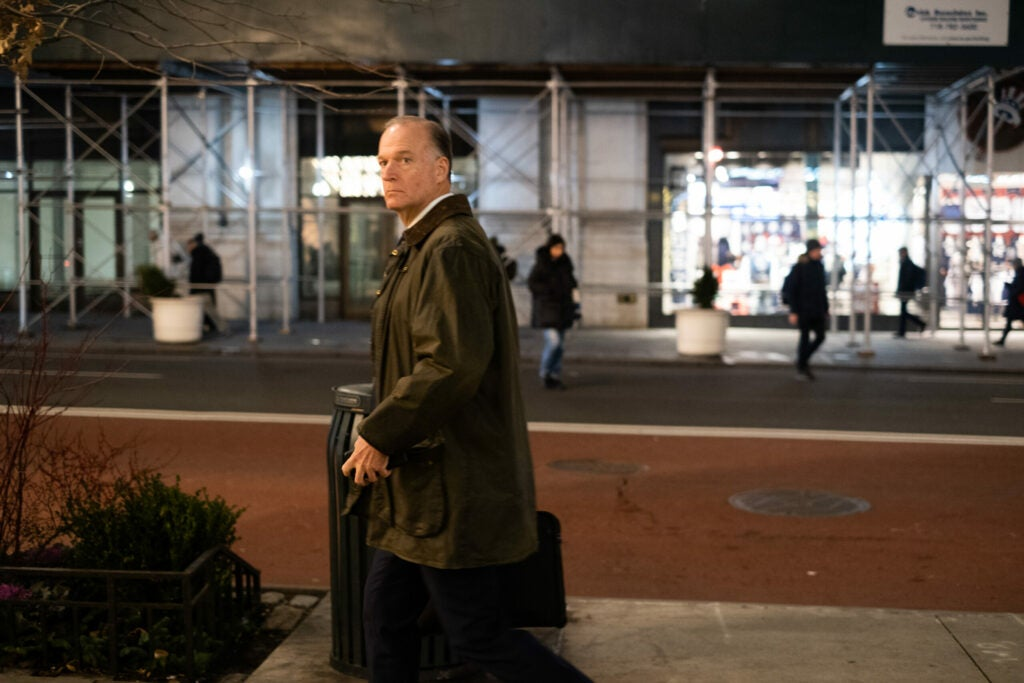 man walking with luggage in coat