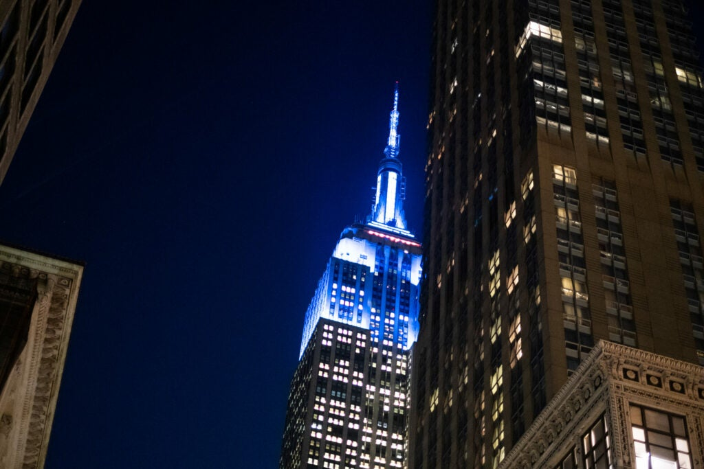 Empire state building lit up blue at night