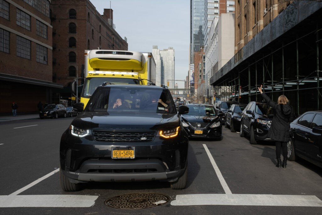 Pedestrian hailing a cab in New York traffic