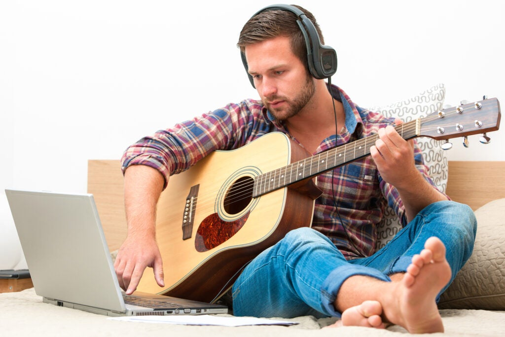 Person on sofa playing the guitar with laptop at home
