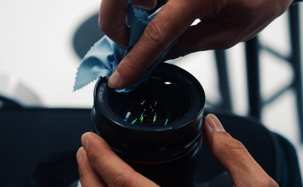 Hands cleaning camera lens