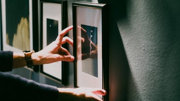 Hands aligning frame on the wall