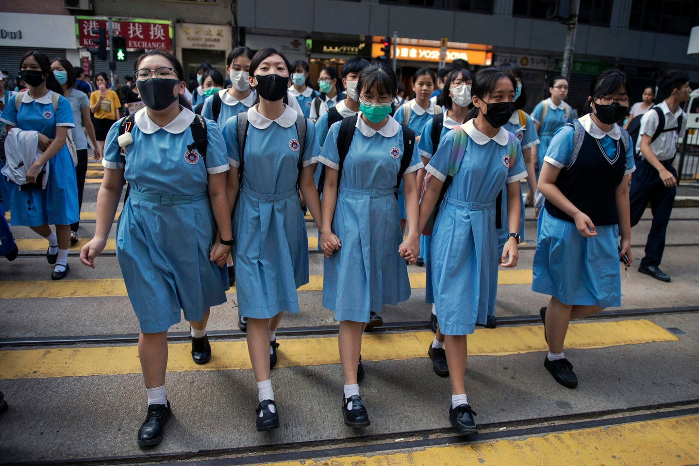 Students cross a road to school after participating in a human-chain rally, in Hong Kong, on 12 September 2019.