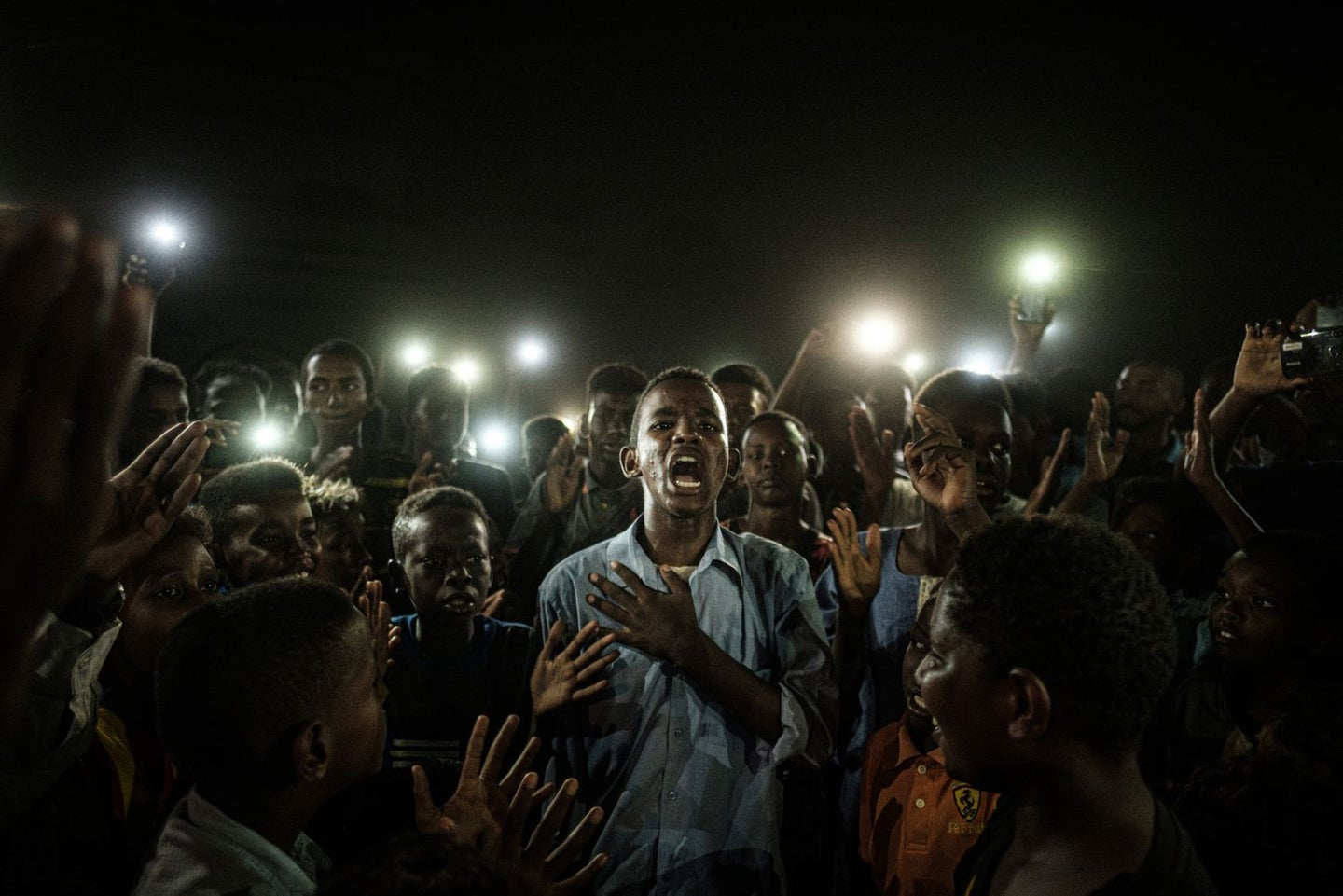 A young man, illuminated by mobile phones, recites protest poetry while demonstrators chant slogans calling for civilian rule, during a blackout in Khartoum, Sudan, on 19 June.