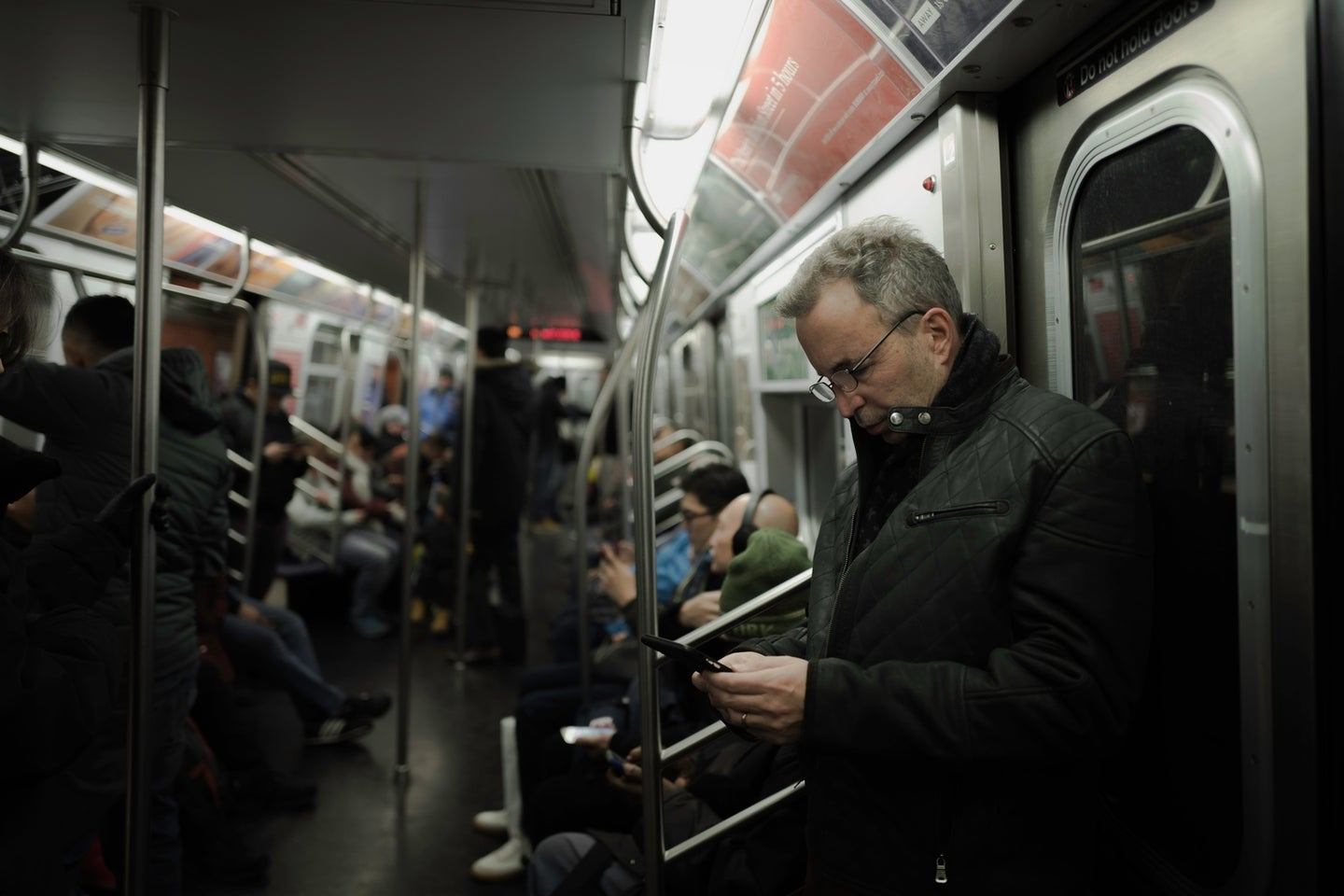 a man using his phone on the New York City subway, while other passengers also use their phones