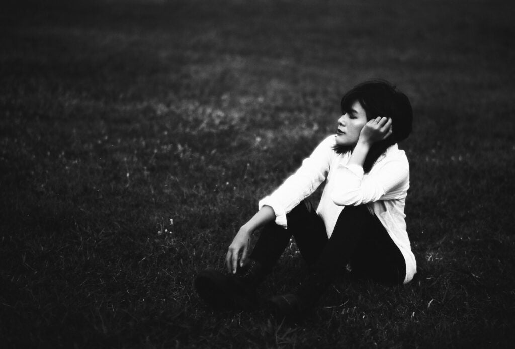 black and white image of woman sitting in grass