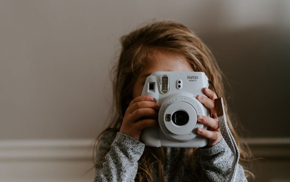A little girl taking pictures with a white round Instant camera in her hand.