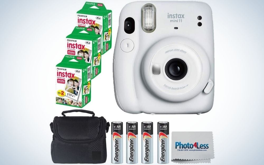 A white and black camera with three small boxes with instax mini and a black bag with a pocket and four silver batteries.