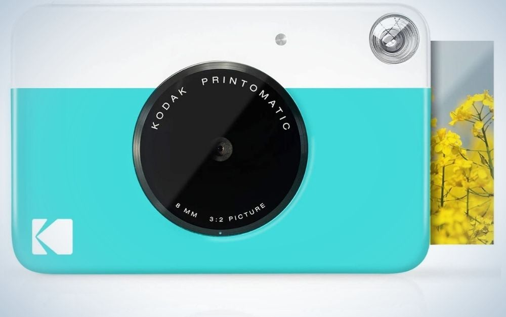 A light blue and white camera from the front with a black lens in the middle of it.