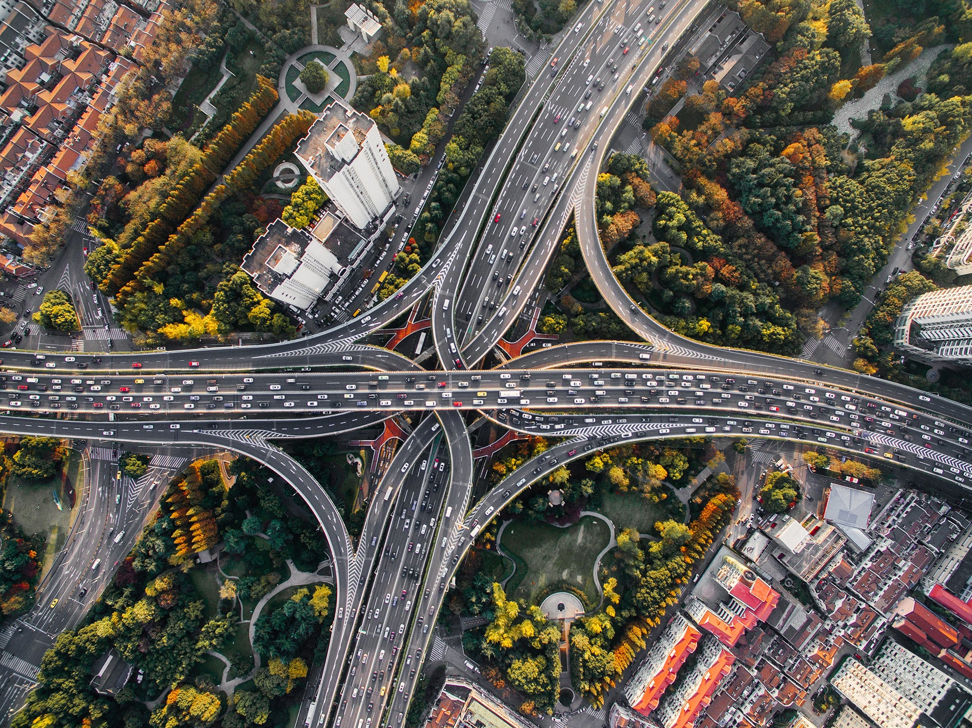 birds-eye view of highway with cars, buildings, and trees