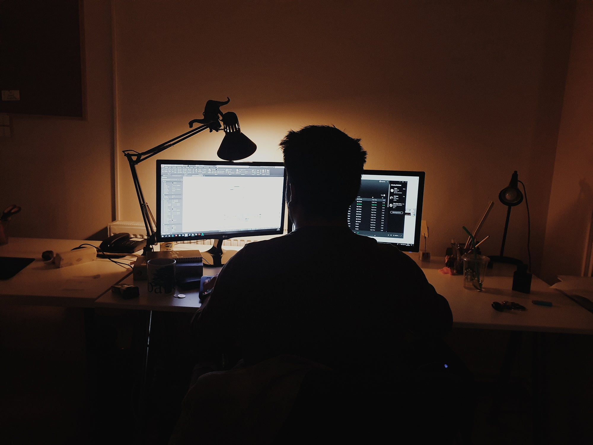 person sitting in a dark room with a lamp and two computer monitors on a desk