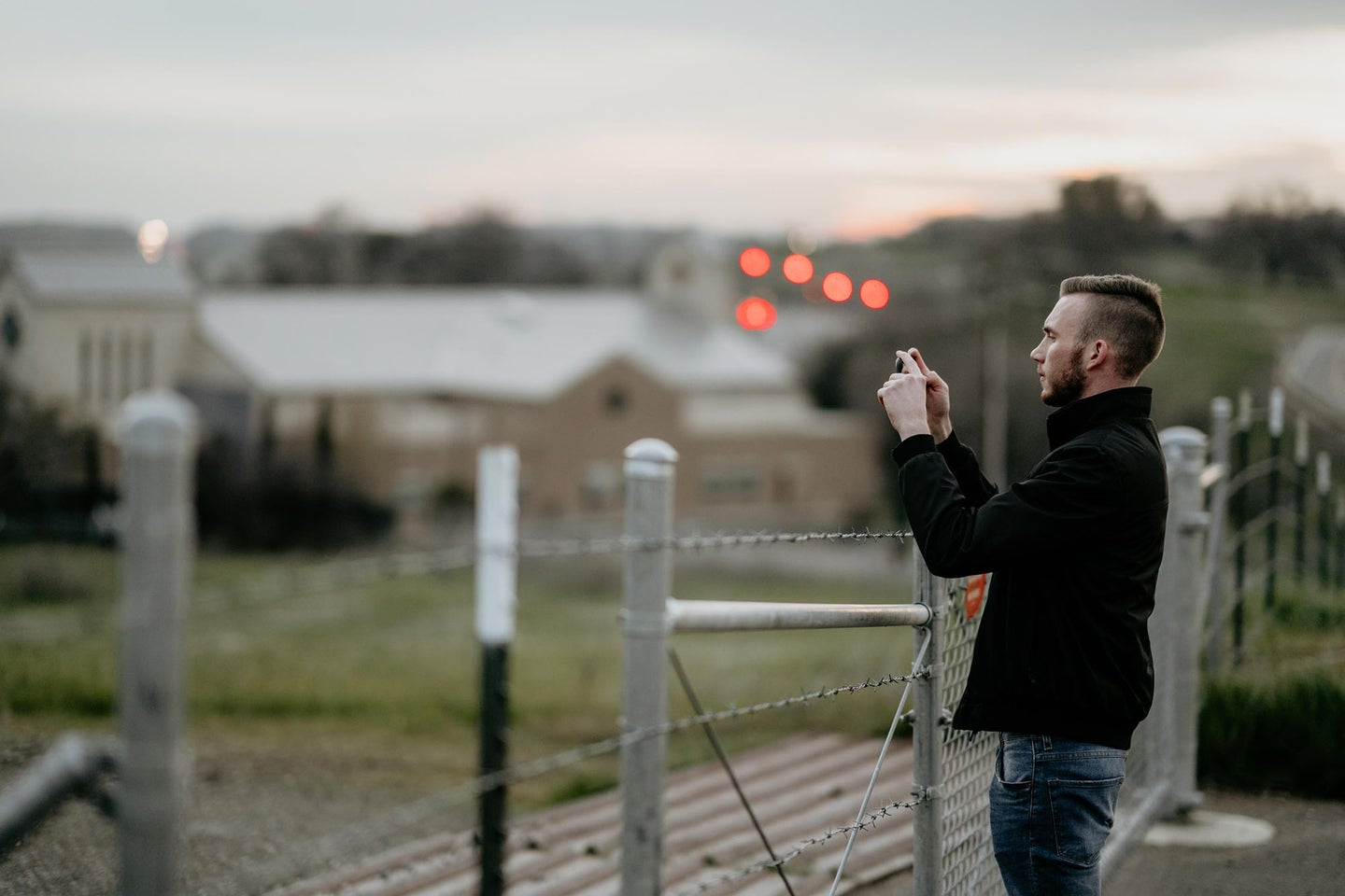 guy taking a photo with the best camera phone on a bridge.