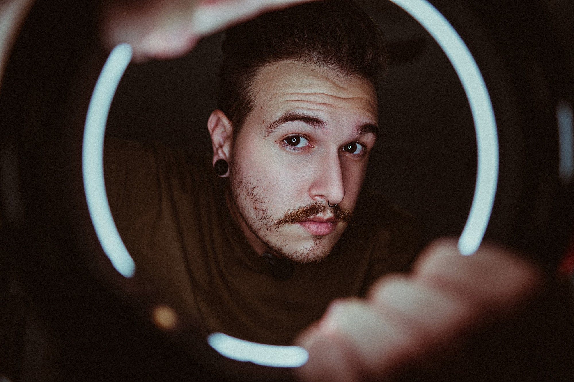 guy with a mustache looking through the best LED ring light