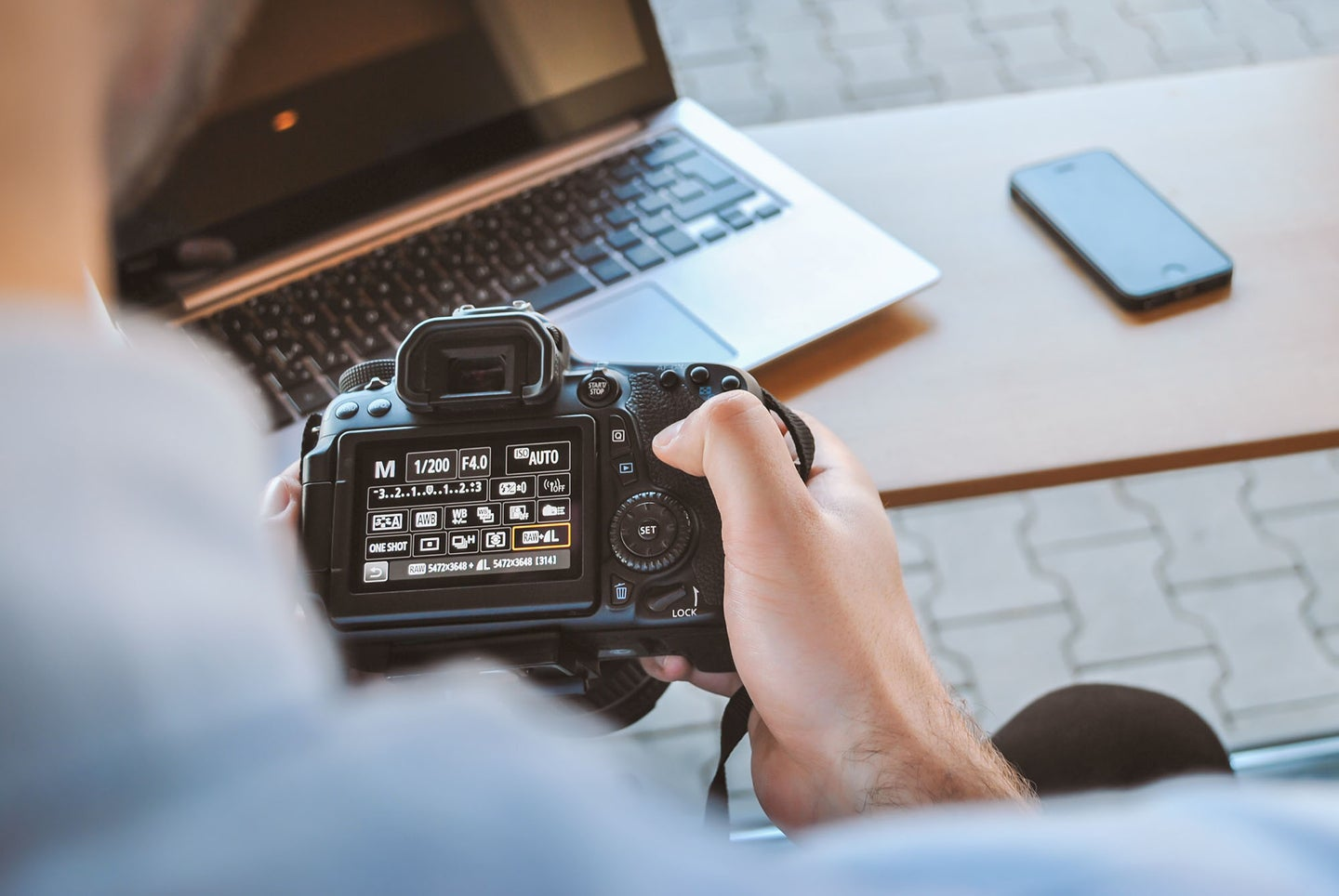person with a camera and the best laptop for photo editing on a desk