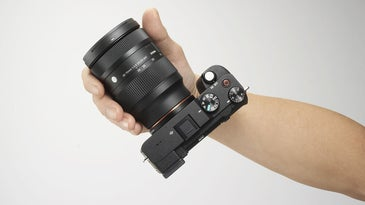 A hand holding Sony's new 28-70mm zoom lens attached to a Sony mirrorless camera body.