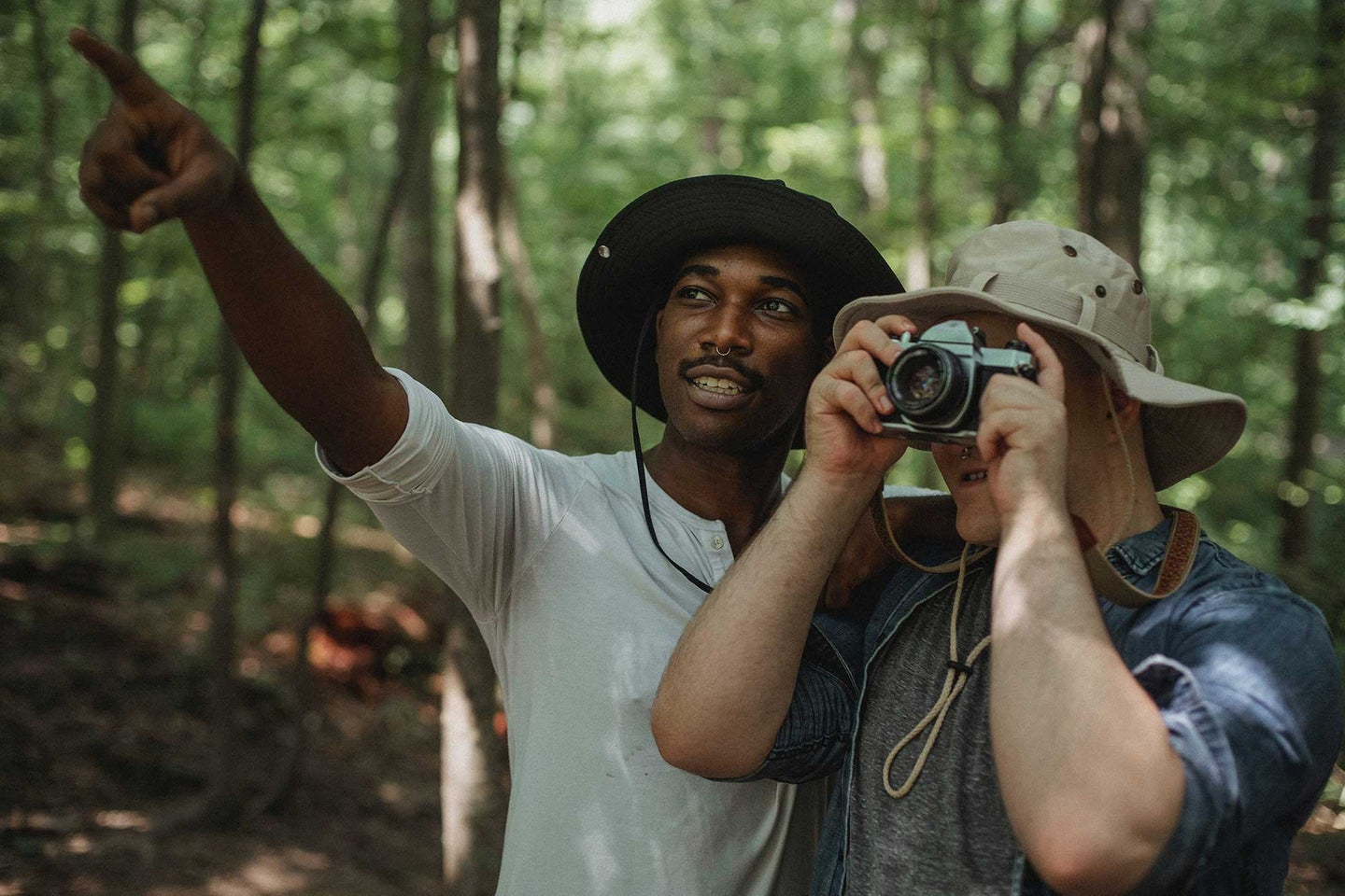 Two men in the woods taking pictures