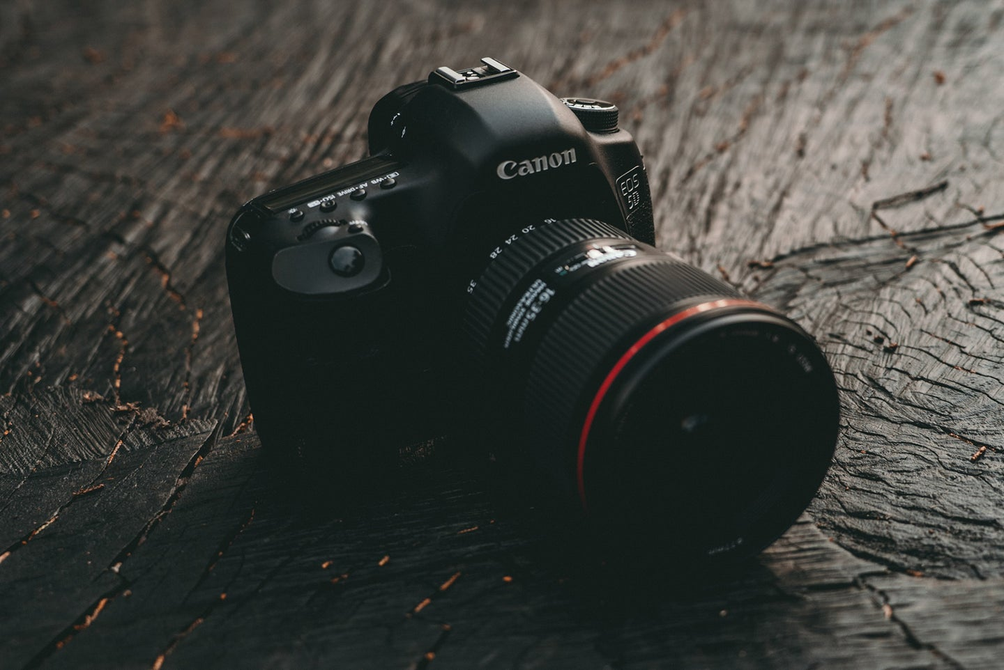 canon camera on a textured wooden surface