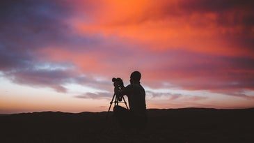 guy with a camera in a tripod with an organge and purple sky behind him
