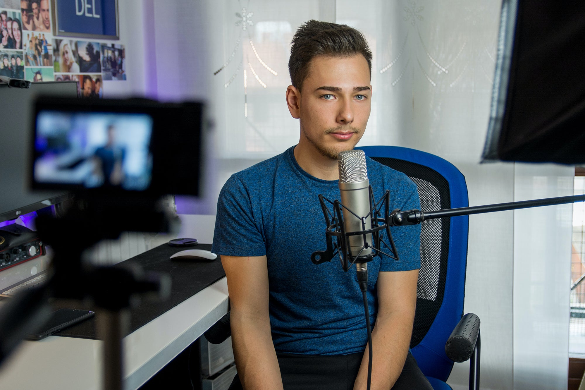 man in front of the best camera for streaming, with a microphone, sitting in a blue chair