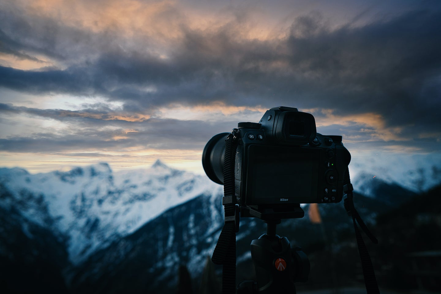 Best full frame camera on a tripod in front of a cloudy sky and snowy mountain