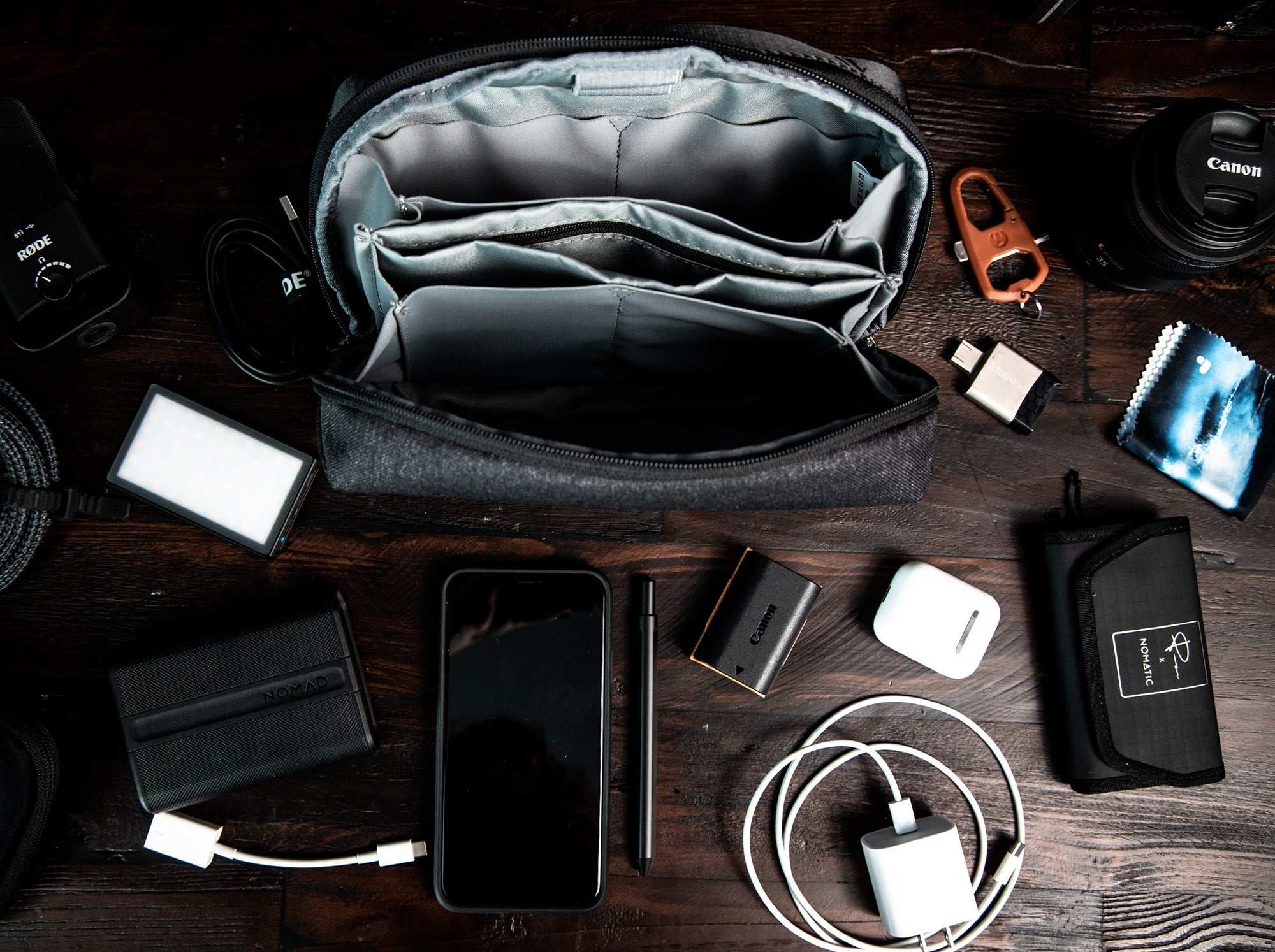 camera, phone, charger, flash drive, and camera bag on a wooden table