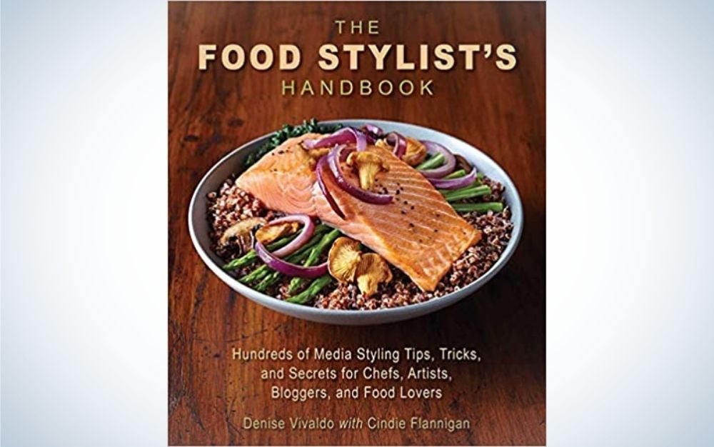 The cover of The Food Stylist's Handbook with brown background and with a cooked salmon plate in the middle of it.