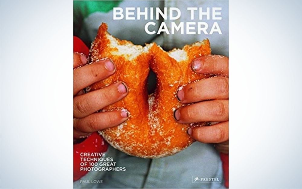 """The hands of a child holding a bitten donut and an inscription that says """"Behind the camera""""."""