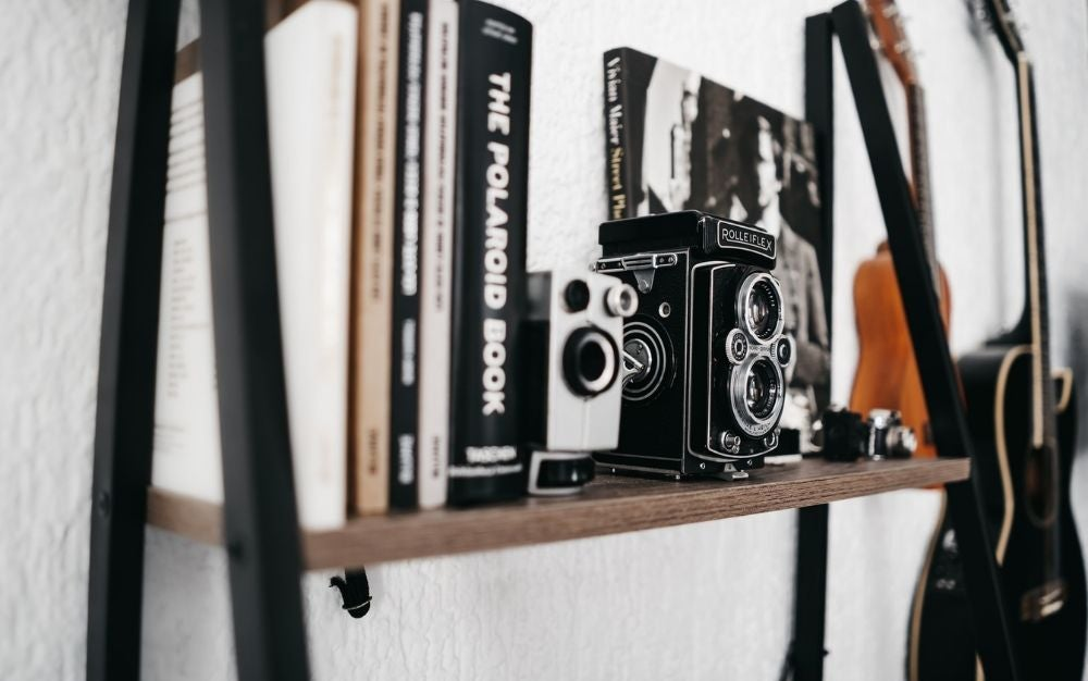 Two photographic cameras between the books lined up on the wall.
