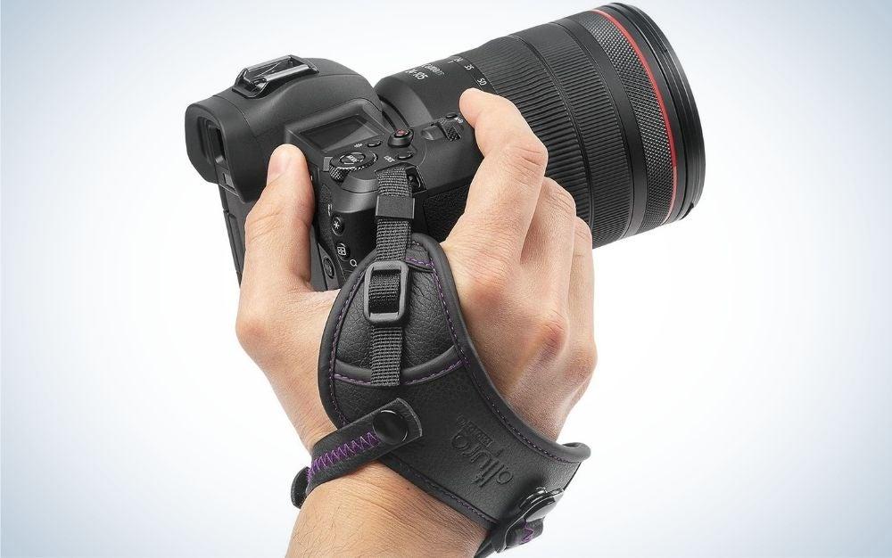 A professional black camera which is in the hand of a man.