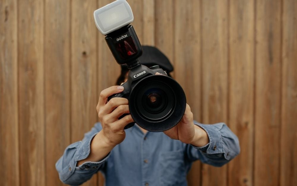 A man using Canon black professional camera in position to take photo.