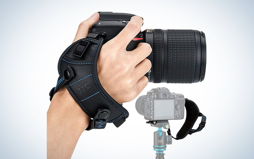 hand holding a camera with a strap