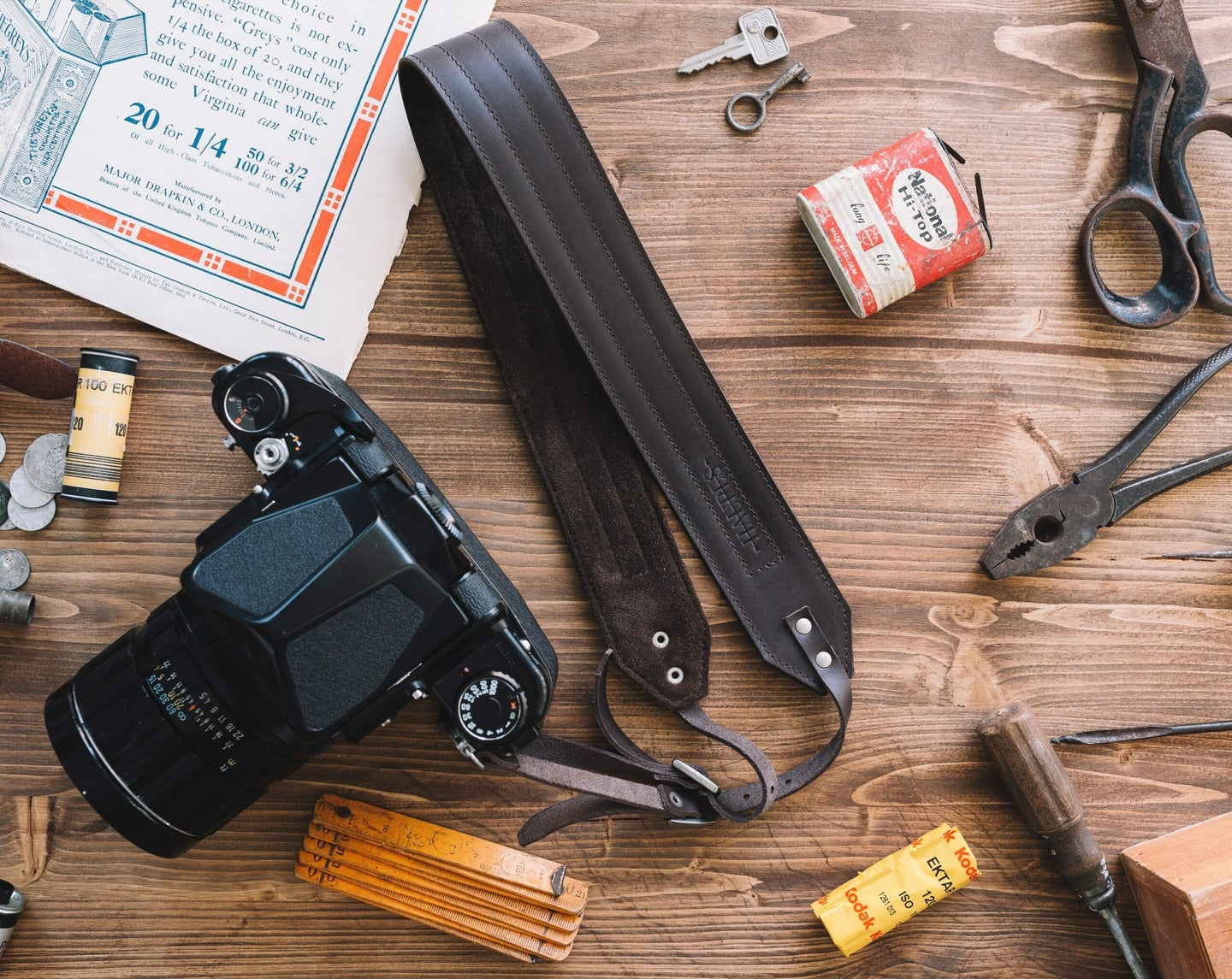 leather camera strap attached to a black camera with the lens, pliers, screwdrivers and meter on a wooden floor