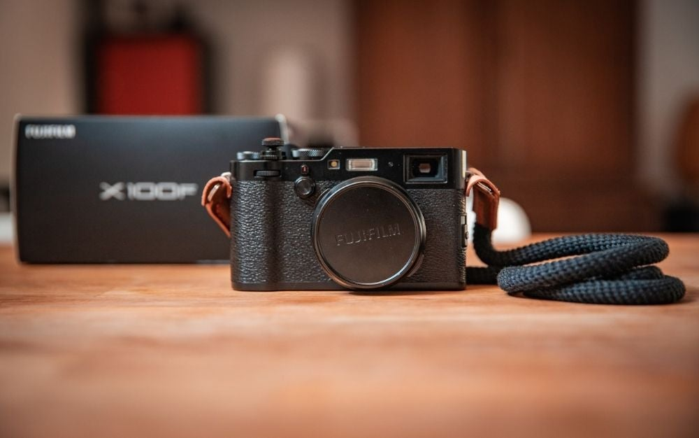 A focused black Fujifilm camera with a neck holder like a black rope resting on a wooden floor with a blurry view from behind.