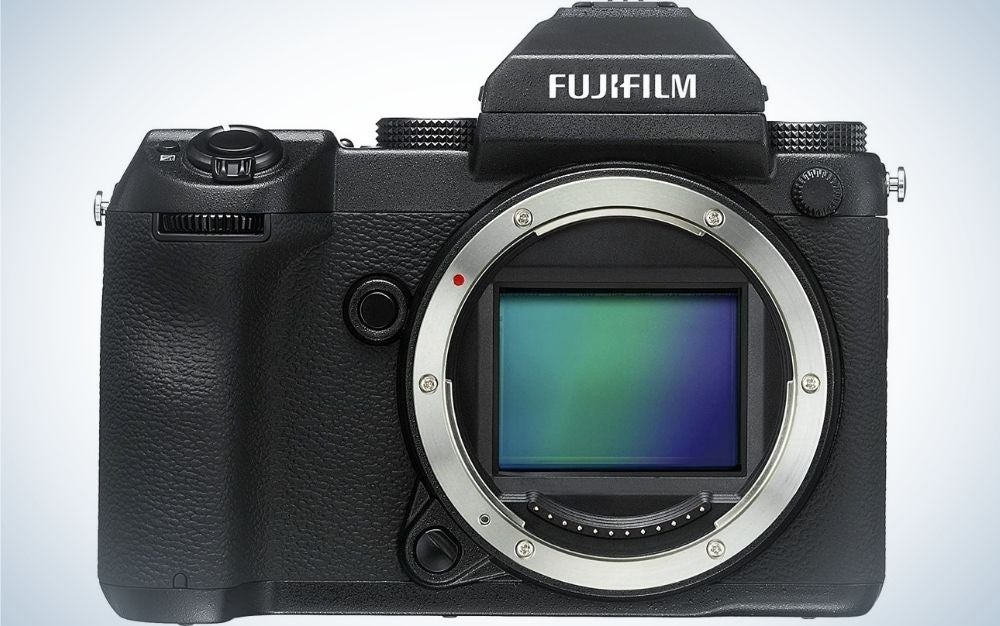 A black Fujifilm camera from the front with the round circle of lens in silver and the lens with blue and green.