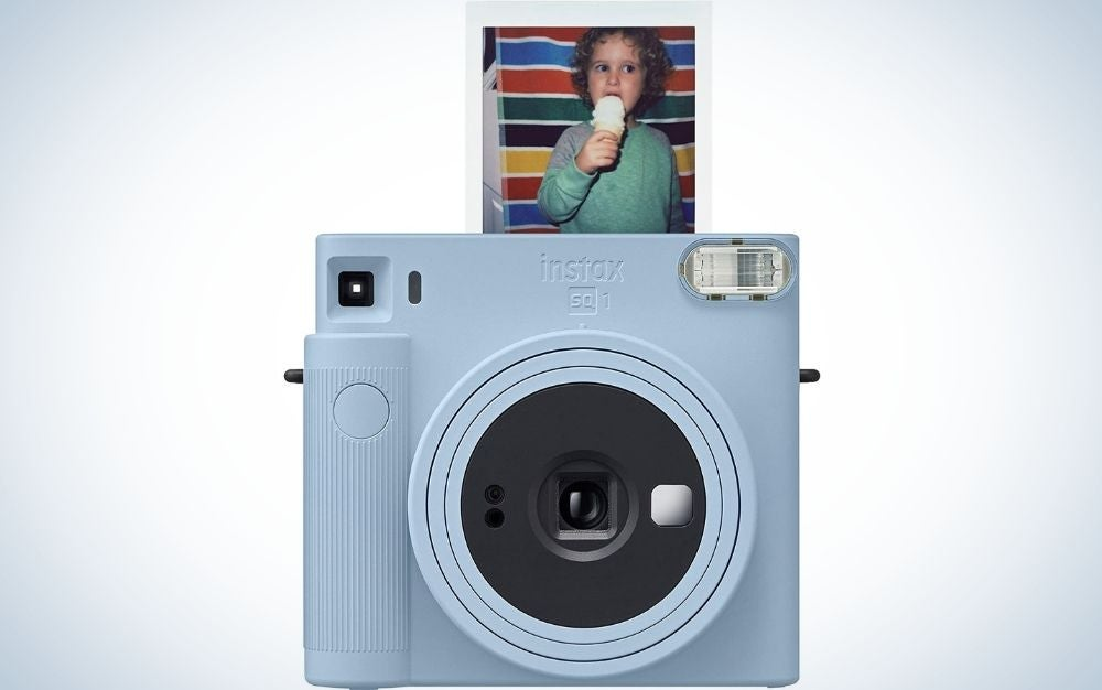 A glacier blue Fujifilm Instax Square SQ1 instant camera in square form from the front with a picture of a toddler eating ice cream on top of it.