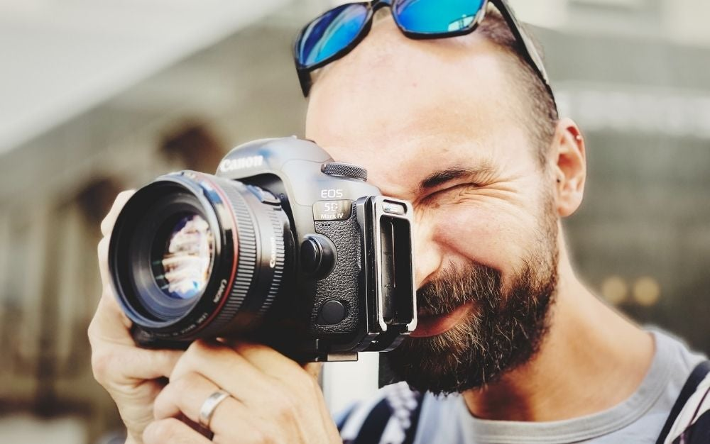 A man with blue sunglasses over his head taking a picture with a professional camera on his hands.