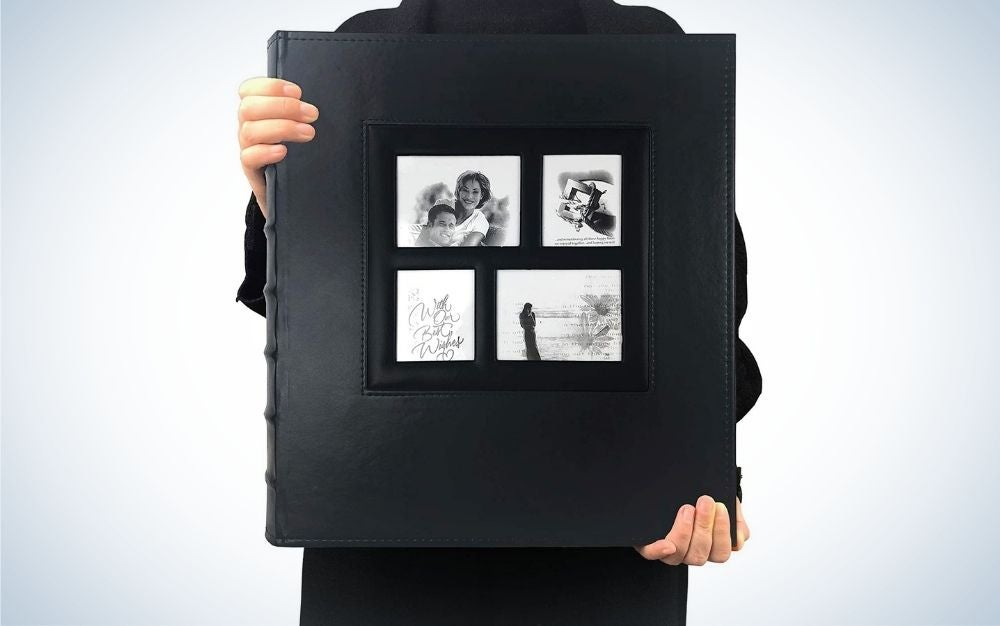 A man holding in his hands a big black photo album with four different photos on it.