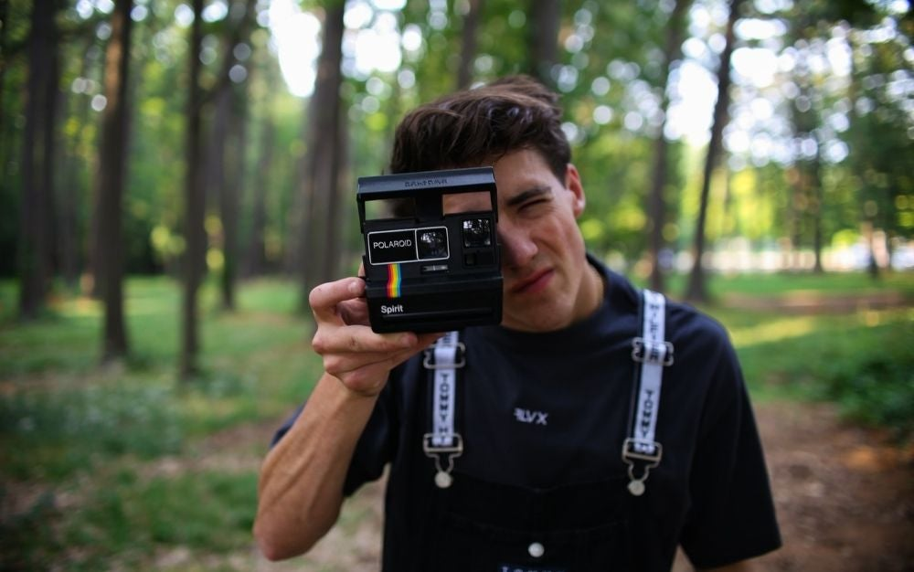 A young man with black shirt with a professional camera on his hands shooting in a forest.