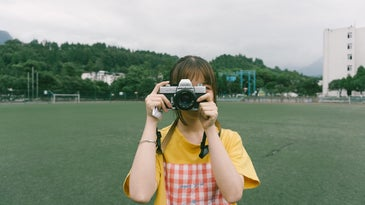 Woman taking a photo with a film camera