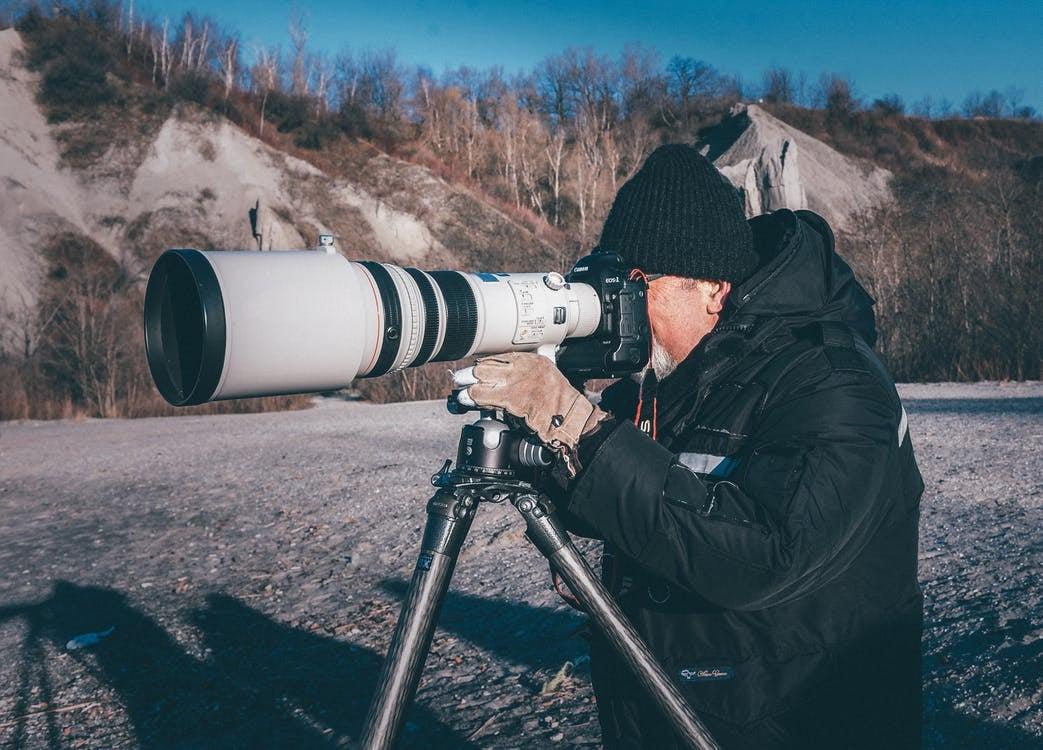 Man using a telephoto lens to take a photo.