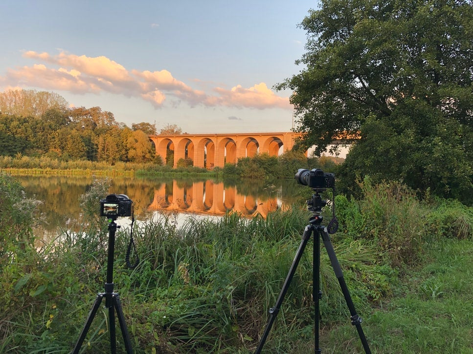 A camera set up on the best travel tripod in front of a lake with a bridge spanning it surrounded by greenery.