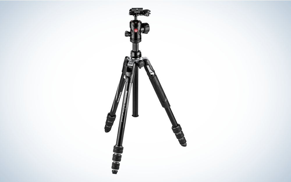 A black compact travel tripod for cameras.